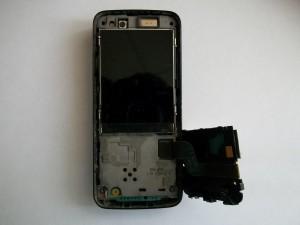Аккуратно, чтобы не порвать шлейф, поднимаем подложку клавиатуры сотового телефона Nokia N82 вправо