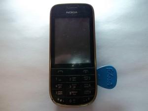 Отщелкиваем медиатором переднюю панель сотового телефона Nokia 202