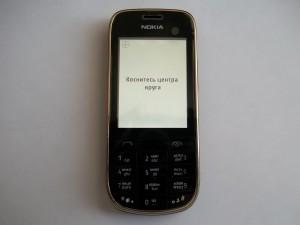 Инструкции на экране сотового телефона Nokia 202 при калибровке экрана