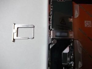 Полностью вытащенный держатель сим карты в сотовом телефоне iPhone 4s