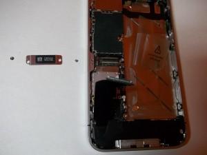 Откручиваем два винта и отсоединяем шлейф в сотовом телефоне iPhone 4s
