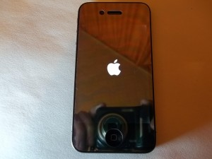 Логотип яблока на экране сотового телефона iPhone 4s